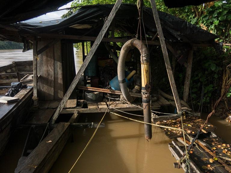 A large tube is used to dredge the riverbeds for gold. Photo by Bram Ebus for Mongabay.