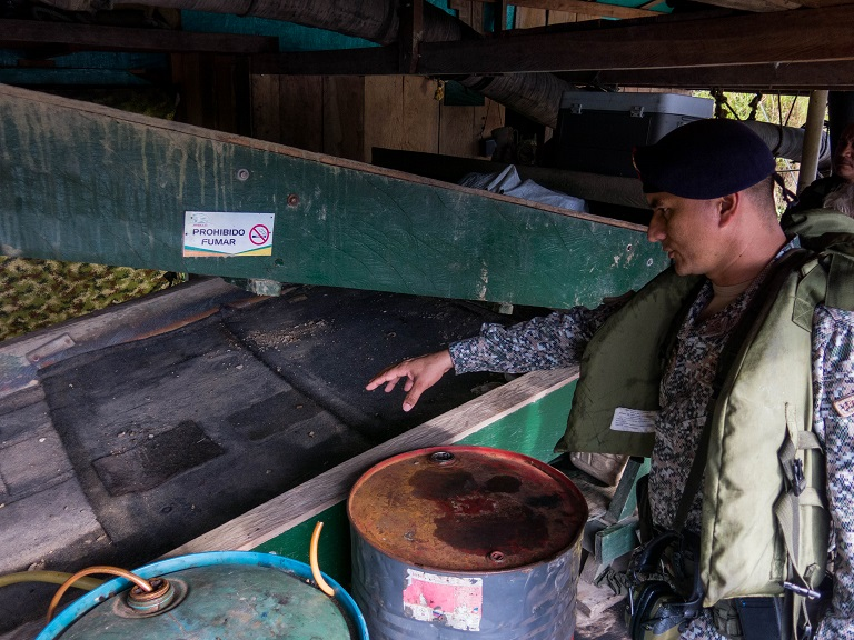 Maj. Edgar Hernándo Jaimes Súarez explains how gold is extracted from the river sediments on a draga. Photo by Bram Ebus for Mongabay.
