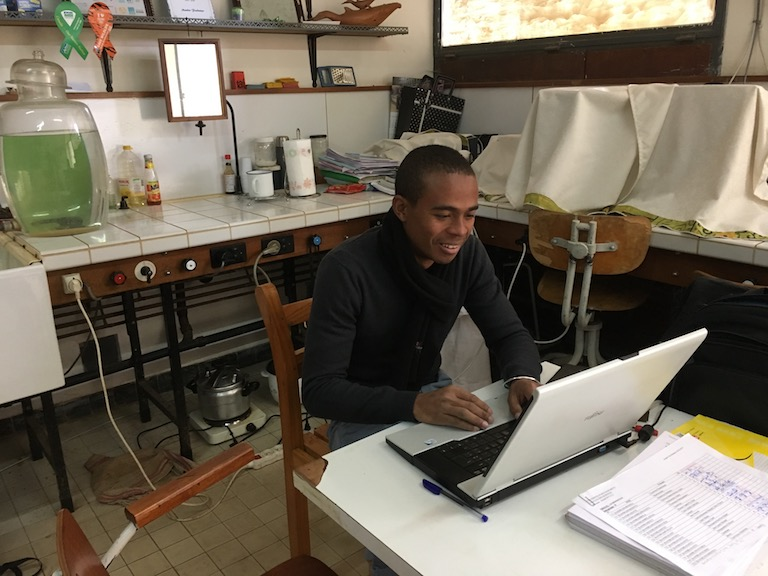 Eric Marcel Temba, a PhD candidate in ornithology, uses a secondhand laptop given to him by a colleague in the UK. Photo by Rowan Moore Gerety for Mongabay.