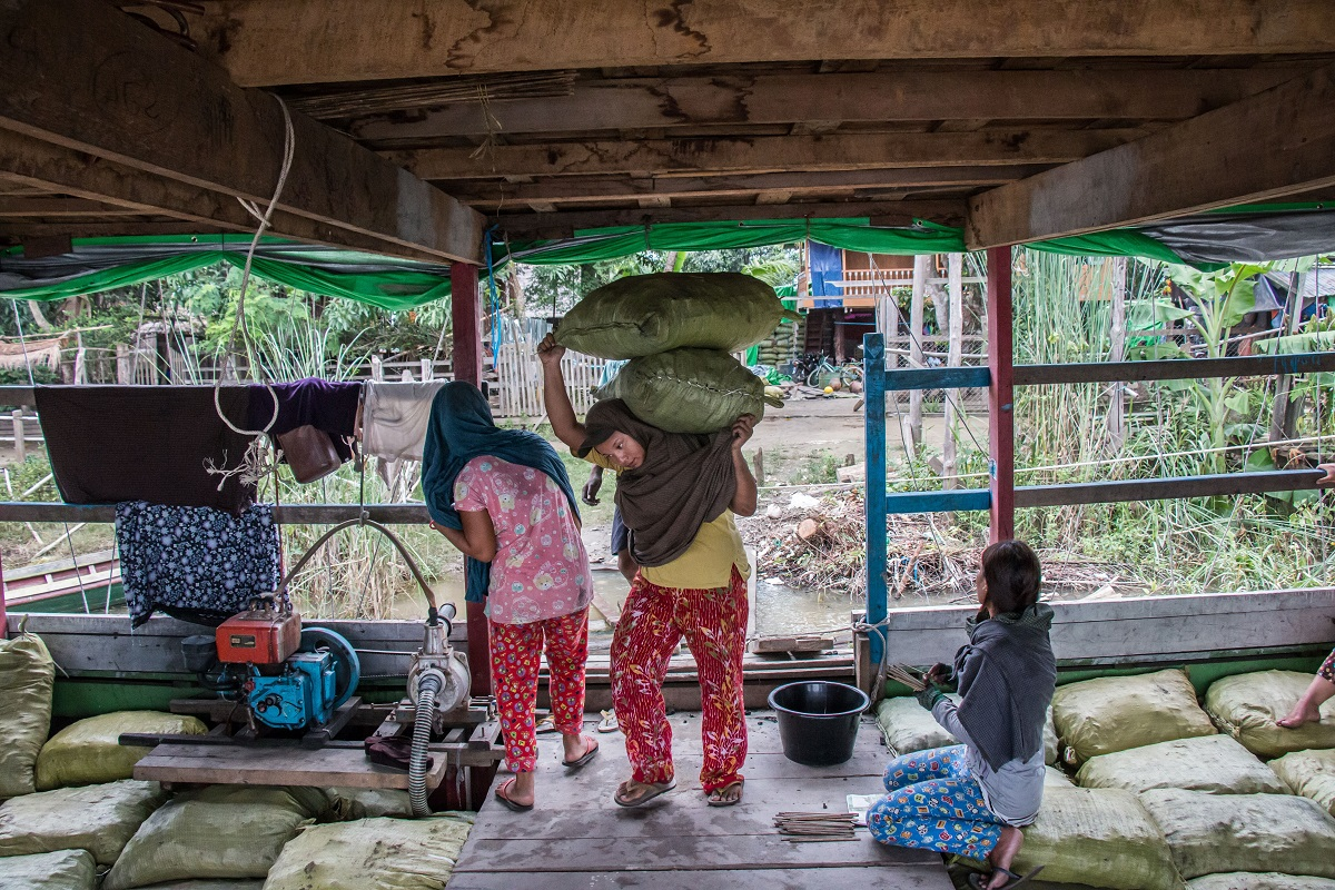 Locals load charcoal bags onto a boat near Katha, Myanmar. The boat is bound for Bhamo, where the charcoal will be taken by trucks over the border to China. Photo by Nathan Siegel for Mongabay.