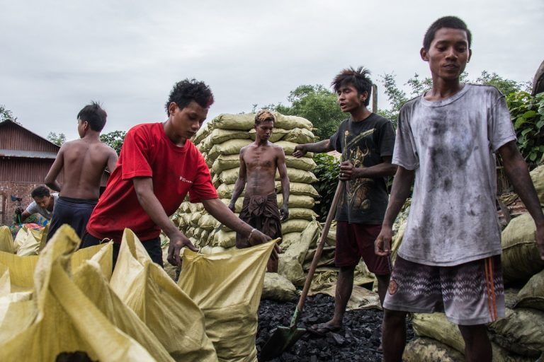 Workers manage hundreds of charcoal bags stored in a lot in Bhamo, Myanmar before they're loaded onto trucks and bound for China 50 miles away. Photo by Nathan Siegel for Mongabay.