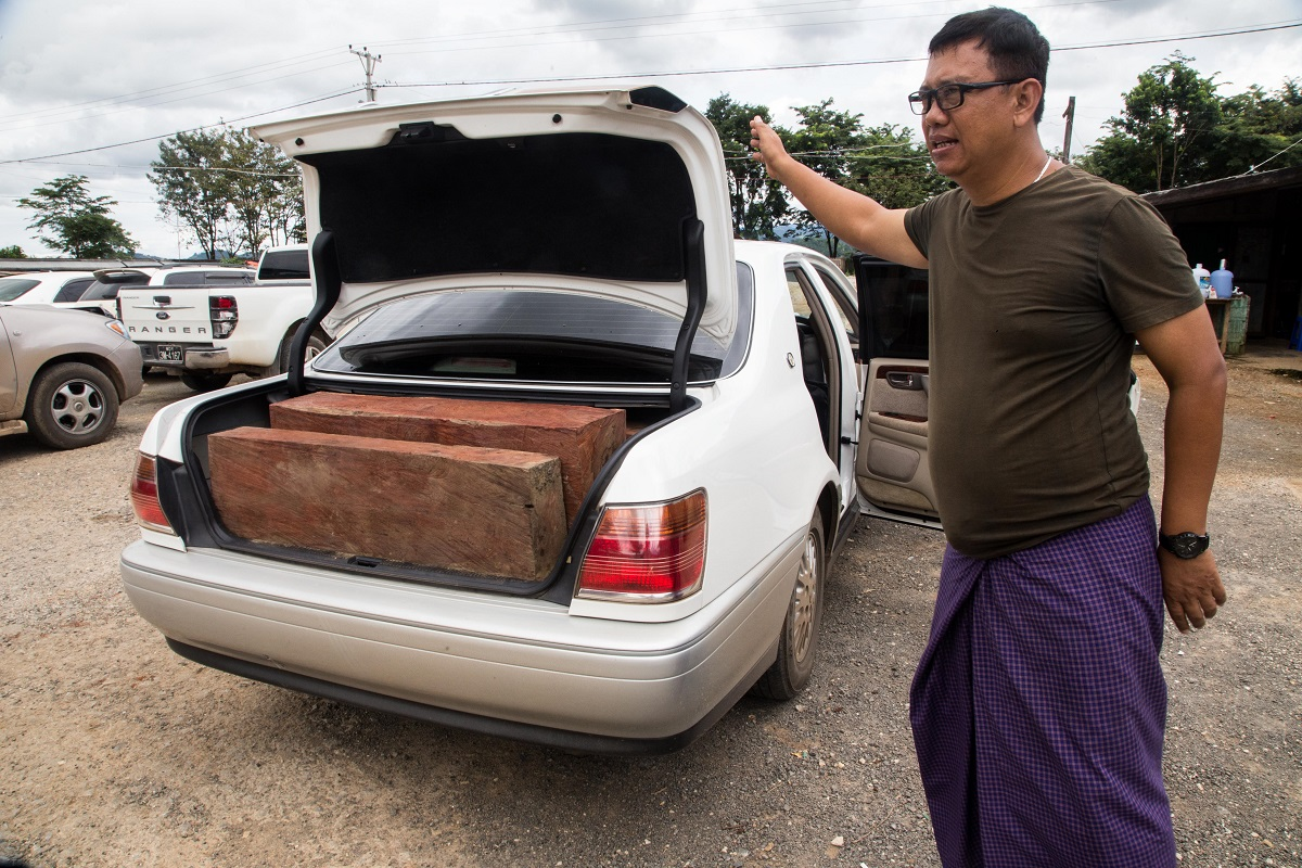 U Tin Myo Aung, assistant director of Yu Pu check point, displaying a seized car loaded with smuggled rosewood destined for China. Photo by Ann Wang for Mongabay.