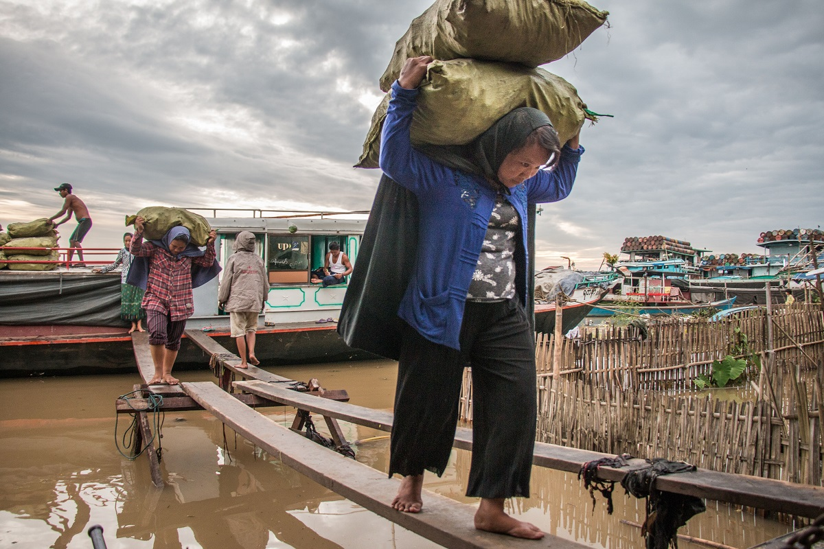 Women unload charcoal from a boat in the town of Bhamo, along the Irrawaddy River. Photo by Nathan Siegel for Mongabay.