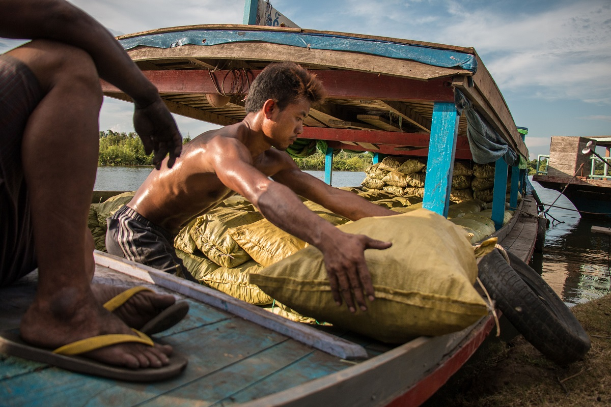 A man loads bags of charcoal onto a boat near Katha. Photo by Nathan Siegel for Mongabay.
