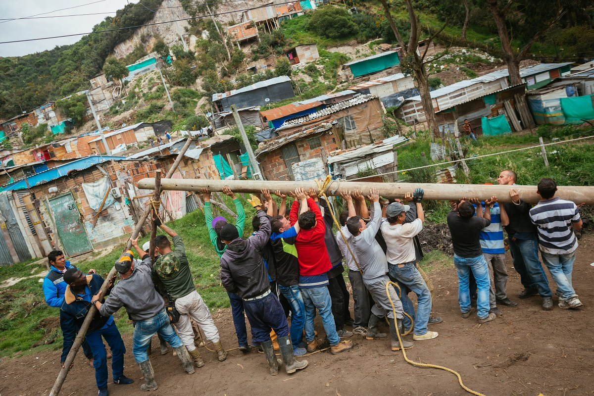 Members of the community work together to install light posts. Photo by Ana Cristina Vallejo with permission.