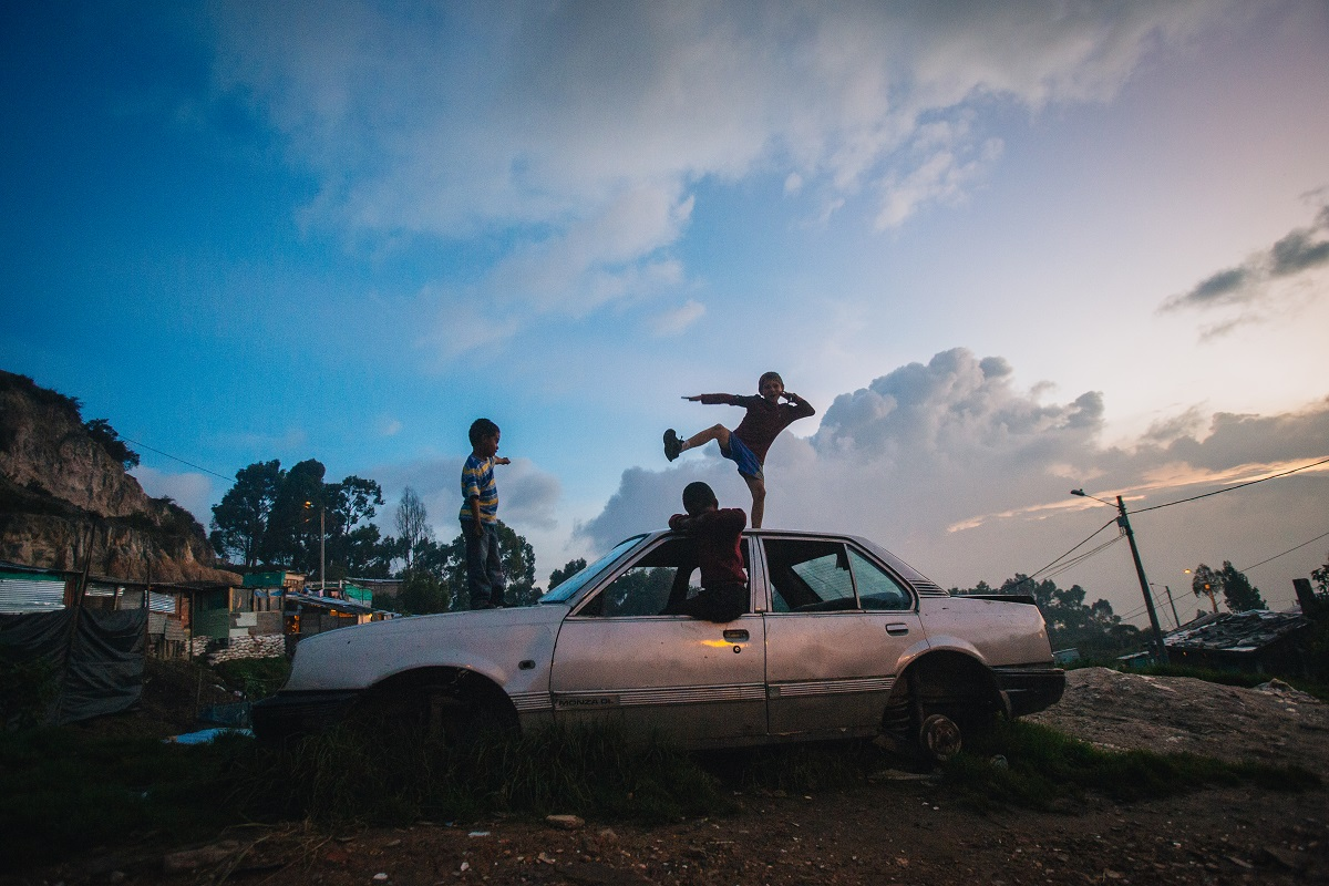 Kids play on an abandoned car as the sun sets over San German. Photo by Ana Cristina Vallejo with permission.