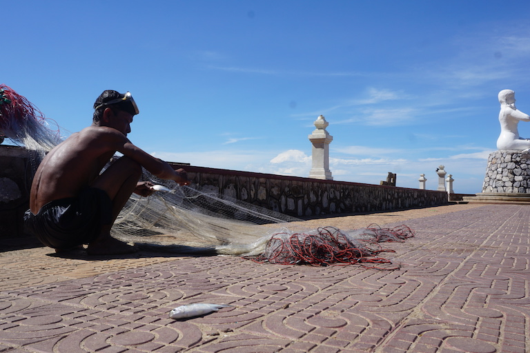 A man pulls a second fish from his hand net on the edge of Kep Bay. All along the coast, subsistence fisherman report increasing difficulty in making ends meet. Photo by Matt Blomberg.