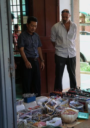Paul Ferber and Sao Sorin, head of the Fisheries Administration branch in neighboring Kampot Province, display banned fishing gear confiscated by patrols. The batteries send an electric charge through the mouth of a trawl net, which is dragged along the seafloor and stuns everything in its path. Photo by Matt Blomberg.
