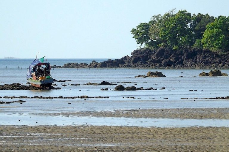 A survey boat used in a 2016 research expedition at low tide. Photo by Christoph Zockler.
