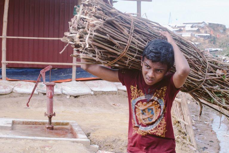 A Rohingya boy carrying a load of firewood through Kutupalong-Balukhali refugee camp in Bangladesh. Photo by Khaamil Ahmed/Mongabay.