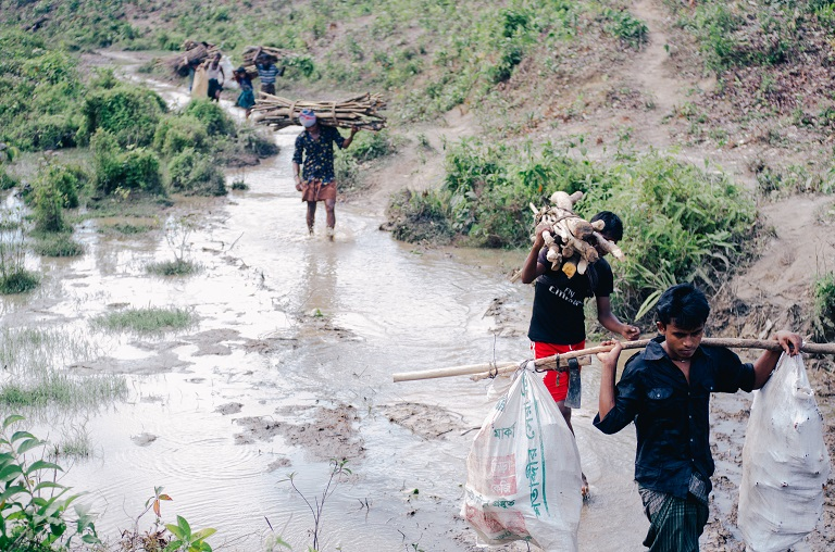 Rohingya men wade through water after heavy rains while returning from collecting firewood. Photo credit: Kaamil Ahmed/Mongabay