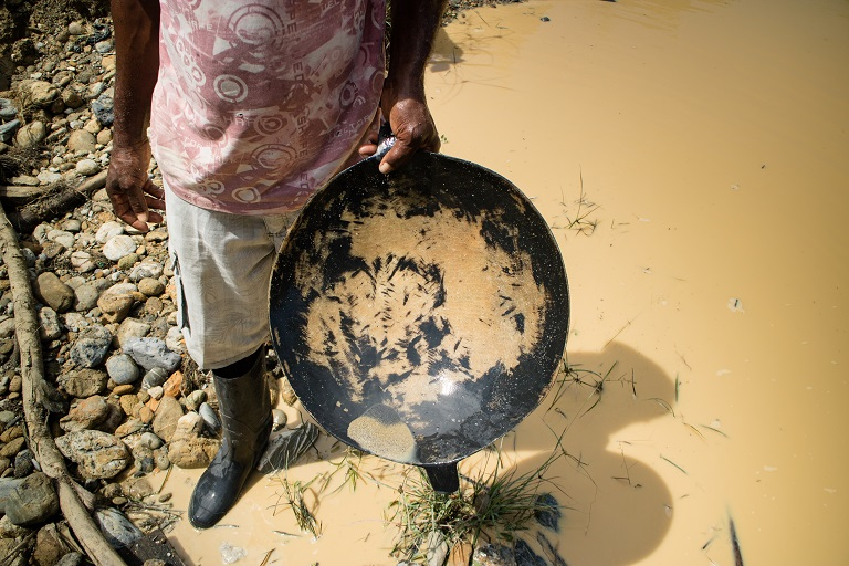A miner holds up a traditional bowl used to pan gold by hand, Noanamá, Chocó. Photo by Maximo Anderson/Mongabay.