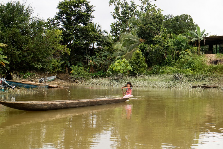 A girl from the Wounaan indigenous community paddles a boat home on the San Juan River, San Juan Basin, Chocó. Photo by Maximo Anderson/Mongabay.