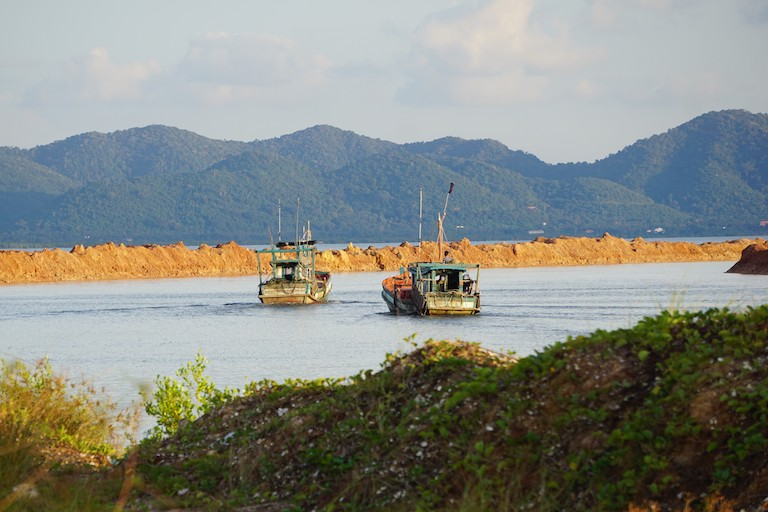 Two trawling boats navigate the construction site for a ferry terminal on their way to sea. The fishermen, who live upriver, now take a different route to their usual hunting ground, where they spend up to 12 hours every evening. Photo by Matt Blomberg for Mongabay.