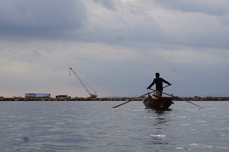 A crab fisherman paddles in front of a port development in Kampot Bay. Several species of crab make their living in the rich, muddy shallows around mangrove forests. Photo by Matt Blomberg for Mongabay.