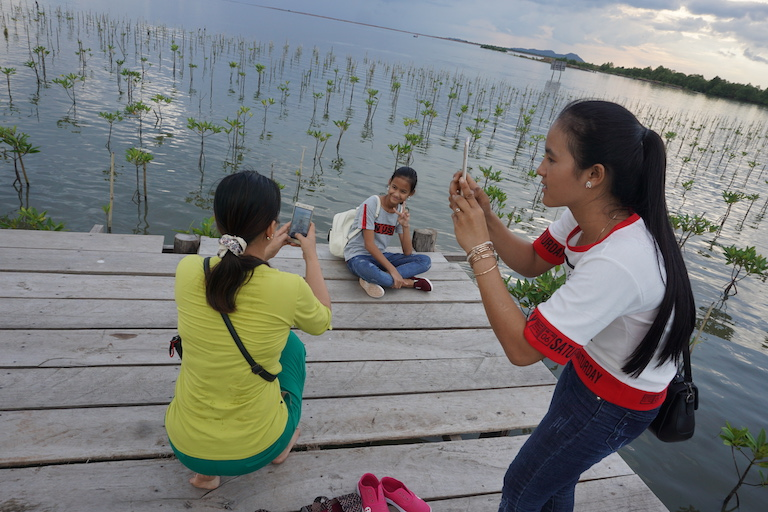 Domestic tourists take photos during a public holiday. The Kampot Mangrove Forest attracts local visitors with boat tours, picnic spots and a restaurant, creating an income to sustain itself. Photo by Matt Blomberg for Mongabay.