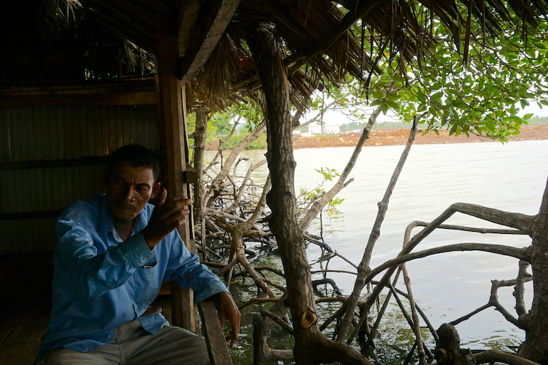 Sin Sen, the village chief at Prey Smach, explains how nearby development has affected his fishing community. On top of destroying mangrove forests, construction of a deep-sea port and oil refinery, visible in the background, is blocking access to fishing grounds and spreading sediments and pollutants. Photo by Matt Blomberg for Mongabay.