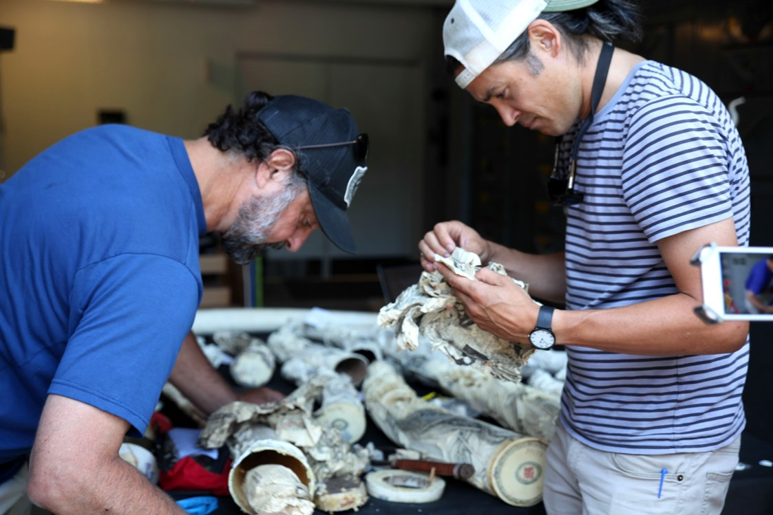 Dr Sam Wasser and Dr Kevin Uno examining ivory carvings while searching for extra clues of their origin.