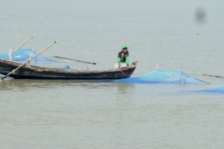A boy uses several mosquito nets to catch fish in the coastal waters near Chittagong, Bangladesh. Photo by R.C. Browmick.