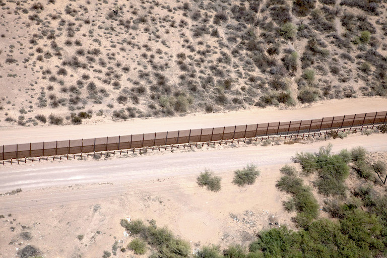 A double row of pedestrian fencing, impassable to non-flying wildlife, and vehicle barrier mark the border in El Pinacate y Gran Desierto de Altar Biosphere Reserve in western Sonora, Mexico. Photo by Rurik List.