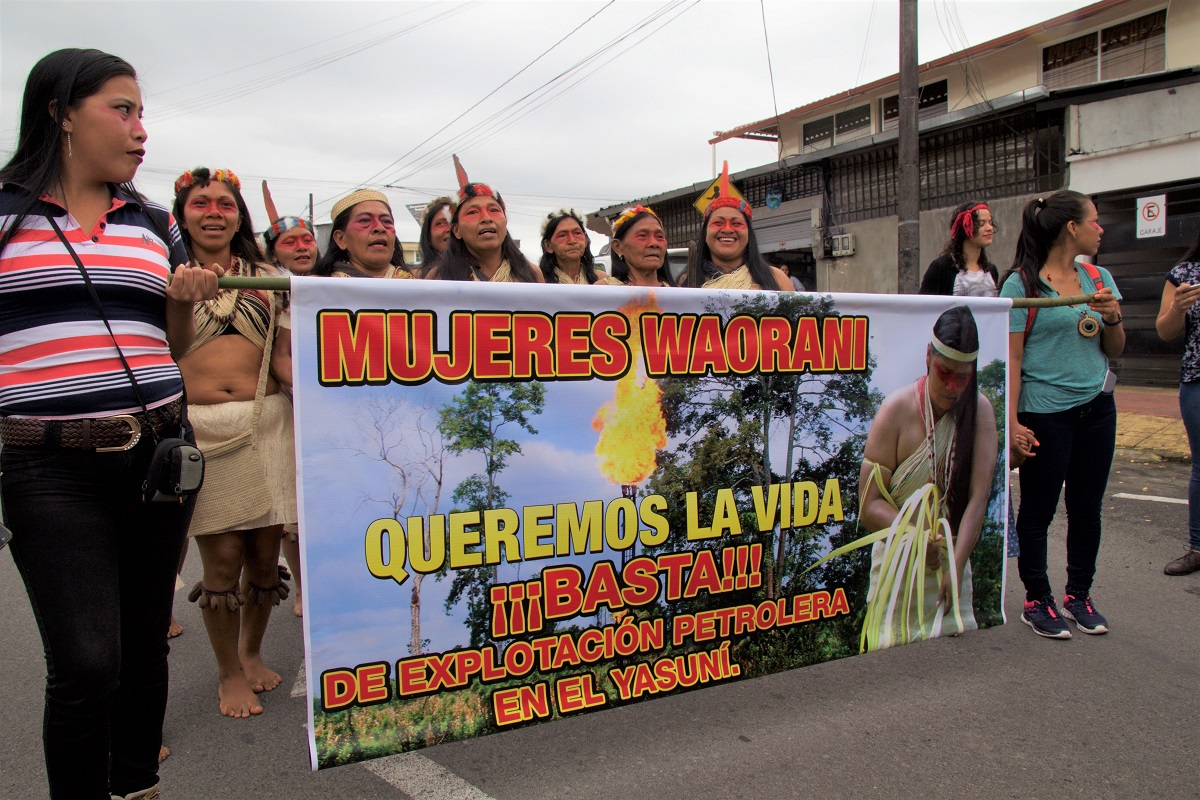 Women of the Amazonian Woarani community carry signs against extractivism in their territory on International Women's Day in the Amazonian city of Puyo, Ecuador on March 8, 2018. Photo by Kimberley Brown/Mongabay.