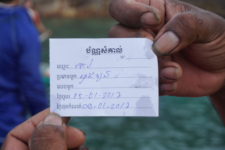 "A Vietnamese fisherman displays a receipt enabling him to fish illegally in Cambodian waters. He said Cambodian authorities gave it to him in exchange for a bribe. The receipt reads ""ID Card / Name: Tev / Boat type: mussel dive / Date entered: 05-01-2017 / Expiry date: 09-01-2017."" Photo by Matt Blomberg."