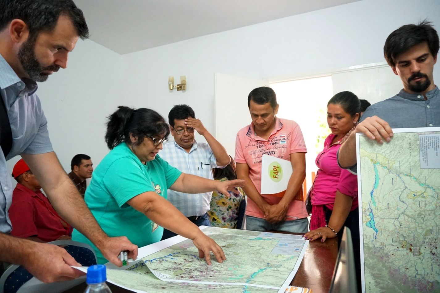 Mirta Pereira, legal advisor of FAPI; Alberto Vázquez; Sindulfo Miranda, president of the Che Iro Ara Poty association, of the Mbya Guaraní people; and Amada Martínez discussing maps during the planning workshop.