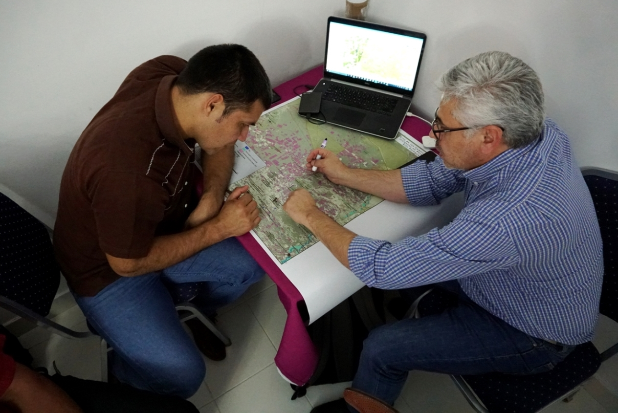 Taguide Picanerai, of the Ayoreo Totobiegosode people, and member of the Organización Payipie Ichadie Totobiegosode (​OPIT), together with Jorge Acuña, GIS technician, of the organization Gente Ambiente y Territorio (GAT), comparing paper and digital maps of the Chaco.