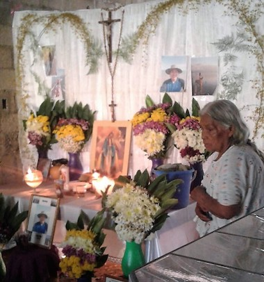 Héctor Choc Cuz's grandmother, Natalia Choc, sits beside photos and flowers honoring her 18-year-old grandson. Image courtesy of the Choc family via Rights Action.
