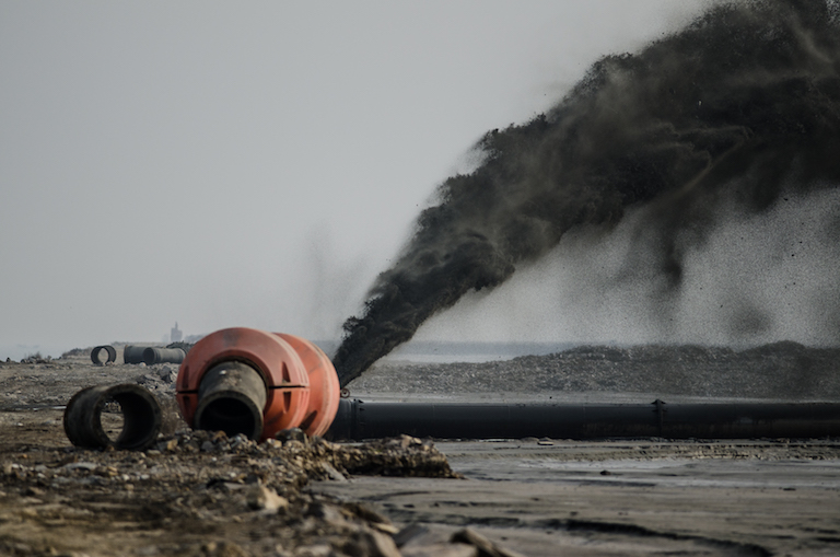 A pump shoots sediment into a coastal embankment along China's Yellow Sea coast, an effort to create solid ground in place of mudflats. Image by Nick Murray, University of New South Wales.
