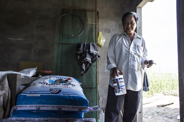 Duong Le, an intensive shrimp farmer in Long An province, Vietnam, with the feed and medical supplements he uses to keep his shrimp healthy. Image by Zoe Osborne for Mongabay.