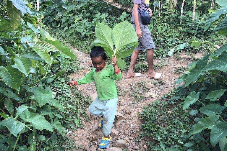 A local child with a leaf. Image by Sarah Hucal for Mongabay.