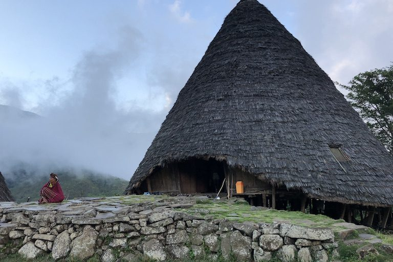 A local in a traditional garment sits outside a drum house. Image by Sarah Hucal for Mongabay.