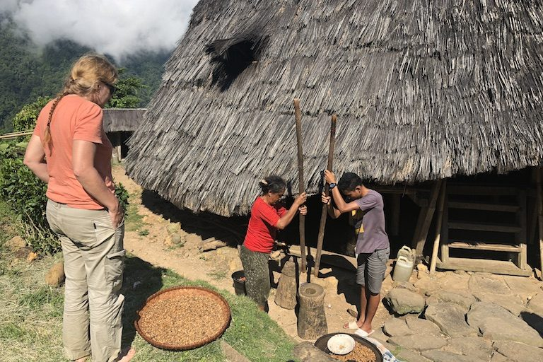 A Belgian tourist looks on as locals grind coffee. Image by Sarah Hucal for Mongabay.