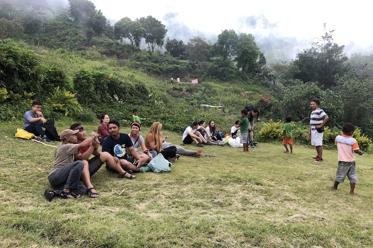 Tourists relax at Wae Rebo. Image by Sarah Hucal for Mongabay.