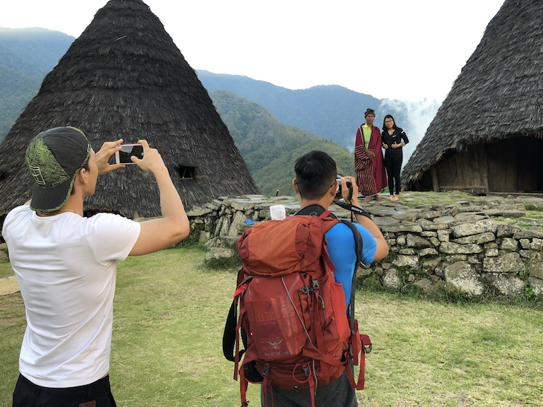 Tourists pose with a resident of Wae Rebo. Image by Sarah Hucal for Mongabay.