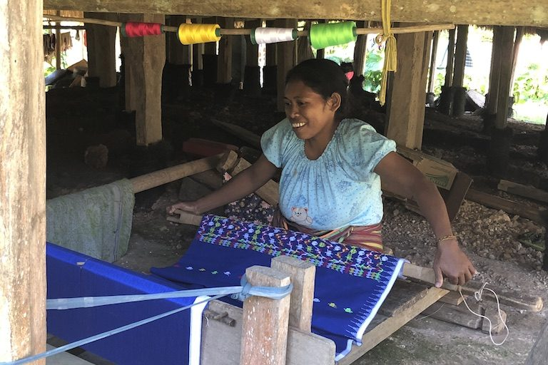 Vilomina Ursula weaves a sarong under a drum house. Image by Sarah Hucal for Mongabay.