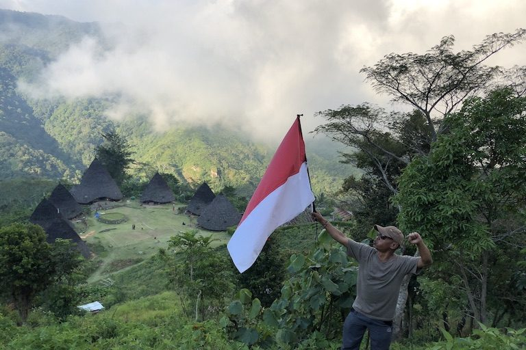 A tourist from Jakarta poses with the Indonesian flag. Image by Sarah Hucal for Mongabay.