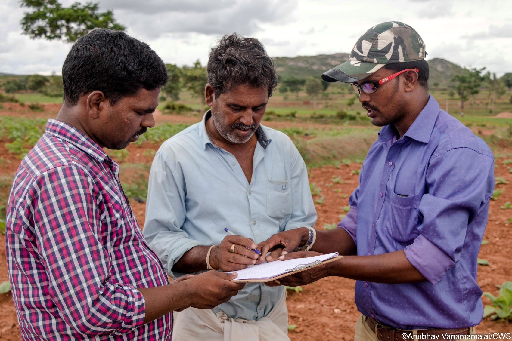 Wild Seve field assistant (right) using the pen and paper method to record villagers' complaints of crop damage by wildlife. Data are now recorded electronically.