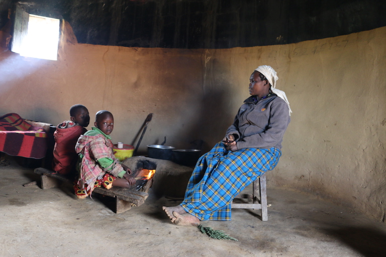 Rosebella Cheruto Kirotich, widow of the late Robert Kirotich who was allegedly shot and killed by Kenya Forest Service officers inside Embobut Forest. She sits inside her house with two of her children. Image by Anthony Langat for Mongabay.