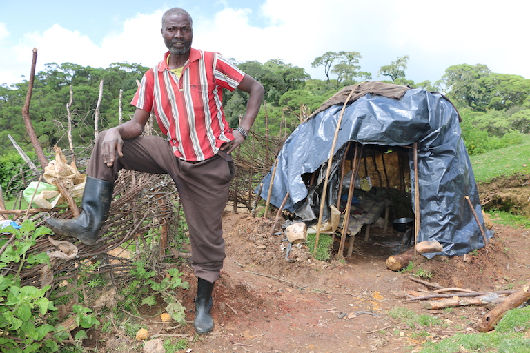 David Kisang stands outside his makeshift hut in Embobut Forest. In 2013 guards with the Kenya Forest Service burned down his houses and granary. His wife and children now live outside the forest for safety, but Kisang remains to look after his cattle and sheep. Image by Anthony Langat for Mongabay.