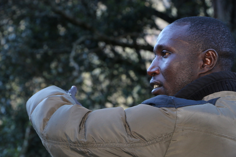 Elias Kimaiyo, a Sengwer activist, points at a bee hive mounted on a tree in Embobut Forest. Image by Anthony Langat for Mongabay.