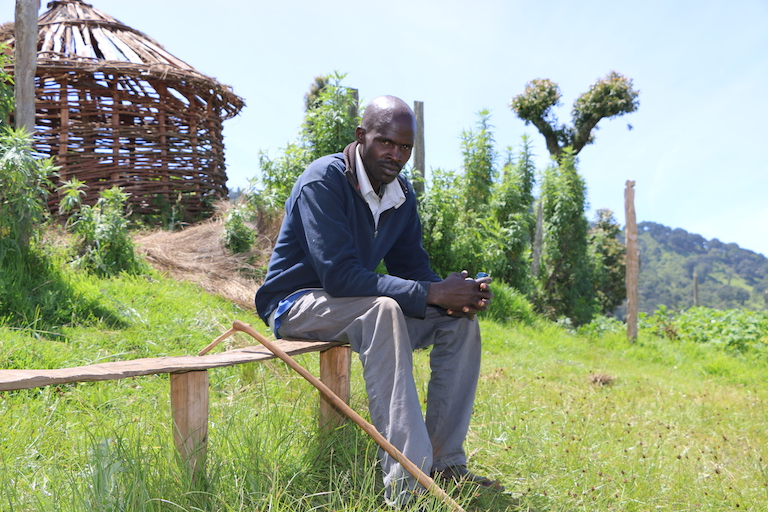 David Koskei was allegedly shot by Kenya Forest Service guards in January, 2018, in an incident that left his friend Robert Kirotich dead. Koskei's leg has yet to fully heal from the wound. In the background is a neighbor's unfinished house. Image by Anthony Langat for Mongabay.