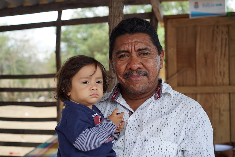 "Elio Uriana, head of the indigenous Wayuu community of Santa Rita Dos, holds his daughter Maria. ""Water is our number one problem,"" he said. ""It is what keeps me awake at night."" Image by Lucy Sherriff for Mongabay."