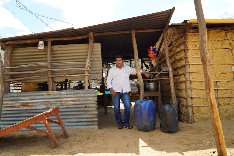 Elio Uriana stands with water barrels, a necessity since water has become scarce. His tribe relies on earnings from weaving bags to pay for water. Image by Lucy Sherriff for Mongabay.