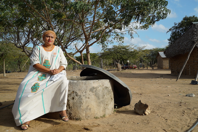María Zapata, leader of the Wayuu community of Persepua, sits on her well. She has seen water levels in the well decline severely in recent years. Image by Lucy Sherriff for Mongabay.