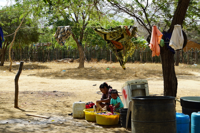 A woman washes clothes with water that is too dirty to drink. Image by Lucy Sherriff for Mongabay.