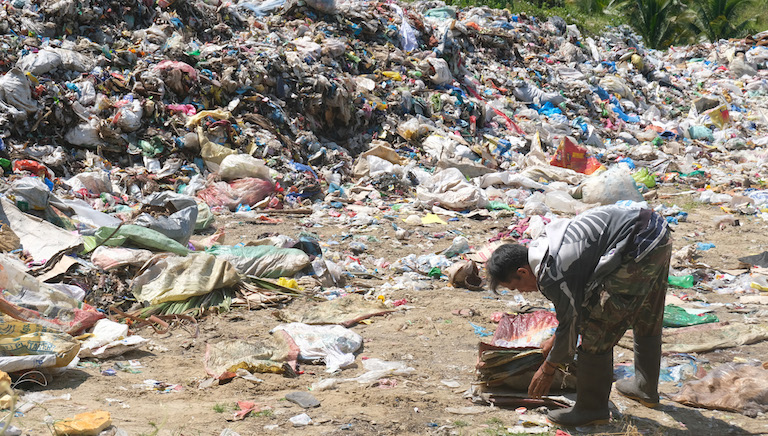 A scavenger collects reusable plastic from the illegal open dumpsite in Malapatan town in the southern Philippines. Image by Bong S. Sarmiento for Mongabay.