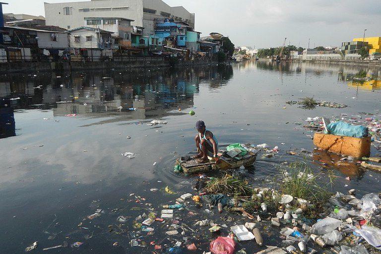 A trash picker plies a Manila waterway. Image by Judgefloro via Wikimedia Commons (CC0 1.0).