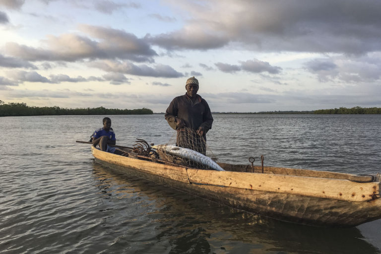 A fisherman pulls in a barracuda at sunset on the waters of the Casamance River, accompanied by an apprentice. Image by Jennifer O'Mahony for Mongabay.